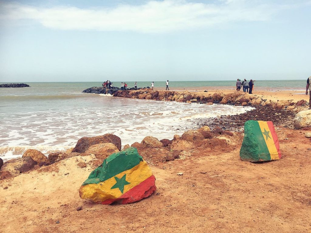 Beach in Saly, Senegal. Senegalese flag painted in two stones. Participants of the francophone forum on the background.