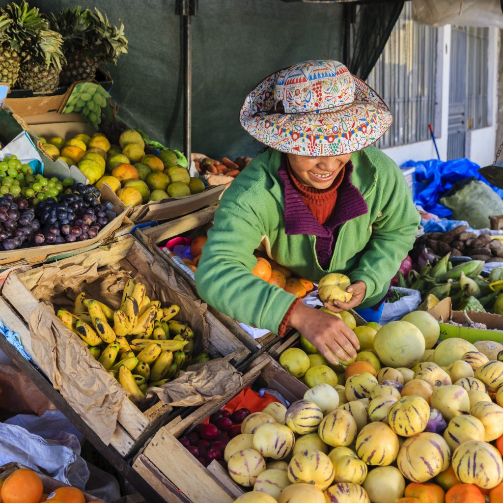 Indigenous Peruvian woman selling fruits in a market