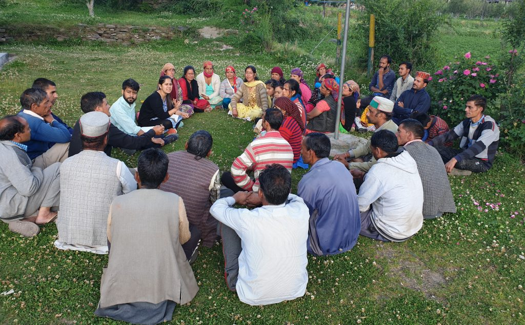 group of Indian farmers seated in a circle.